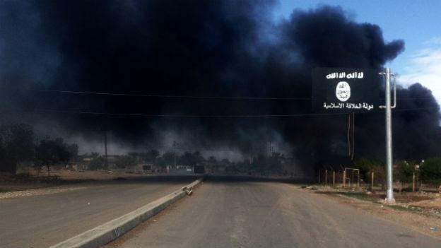 Rauch auf einer Strasse mit IS-Flagge.