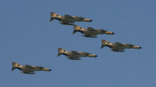 Fünf iranische Kampfflugzeuge fliegen in synchroner Formation.