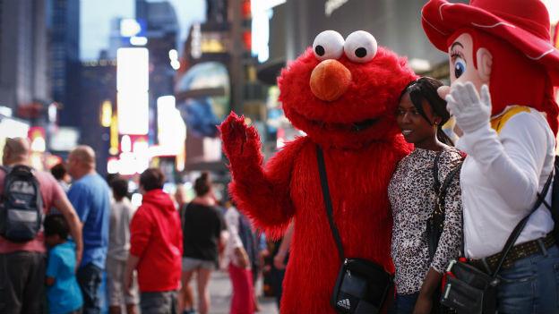 Jorge, ein Immigrant aus Mexiko, posiert mit einer Touristin am Times Square in New York. Er hat sich als Figur Elmo aus der Sesamstrasse verkleidet.