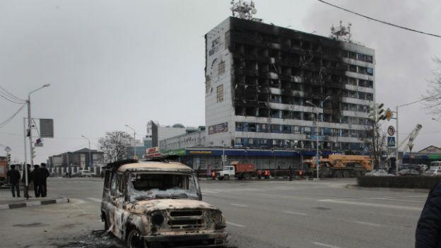 Das Bild zeigt ein ausgebranntes Auto vor einem ausgebrannten Hochhaus in Grosny.