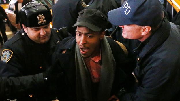 Ein schwarzer Mann wird von zwei Polizisten in Uniform festgehalten.