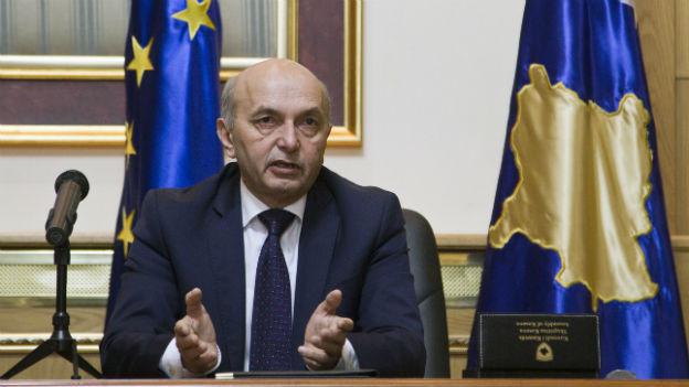 Isa Mustafa, Chef der ehemaligen Oppositionspartei sitzt vor einer Kosovo-Fahne.