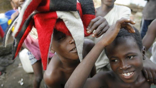 Schwarze lachende Kinder spielen mit einem roten Hut.