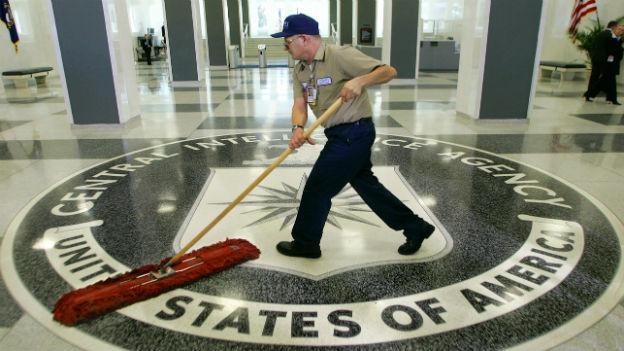 Ein Man putzt den Boden im CIA-Gebäude mit dem eingravierten CIA-Logo.