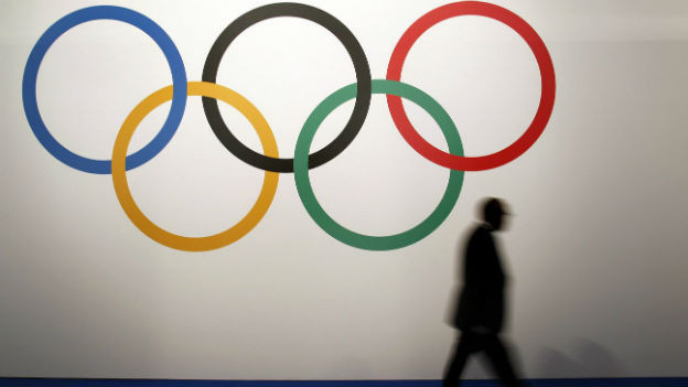 Aufnahme eines Mannes, der an den Olympischen Ringen vorbei geht bei der IOC-Sitzung in Monaco.