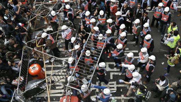 Im Zentrum Hongkongs räumen Arbeiter Barrikaden in einem Gebiet weg, das von pro-Demokratie-Aktivisten blockiert wird.