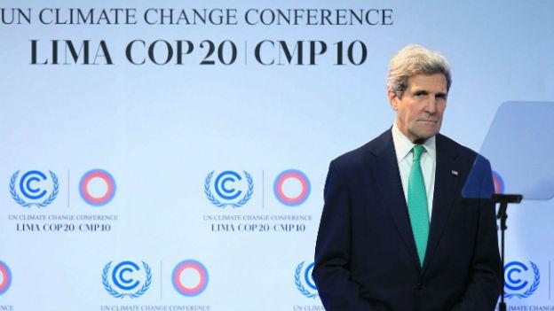 Aussenminister John Kerry steht vor dem Logo des Klimagipfels.
