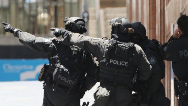 Polizisten in Kampfmontur stehen mit dem Rücken zum Betrachter. Zwei Polizisten zeigen mit der jeweils linken Hand auf einen Punkt ausserhalb des Bildes.