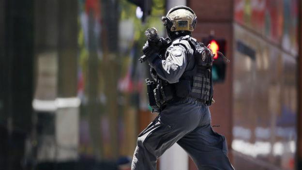 Ein Polizist in Kampfmontour rennt über eine Strasse.