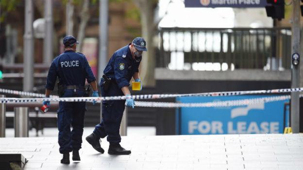 Zwei Polizisten laufen hinter einem Absperrband umher, einer zeigt mit dem Finger auf den Boden.