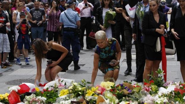 Drei Frauen legen Blumen nieder, im Hintergrund weitere Menschen und ein Polizist.