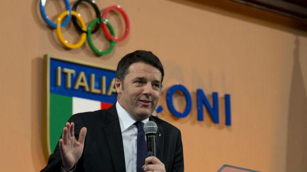 Der italienische Regierungschef vor italienischer Flagge und olympischen Ringen.