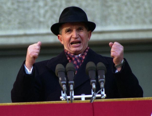 Ceausescu mit Hut und geballten Fäusten vor vier Mikrofonen.
