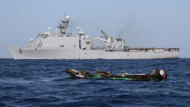 Aufnahme eines verlassenen Schnellbootes von Piraten, im Hintergrund ein US-Frachtschiff, in den Gewässern vor der Küste Somalias.