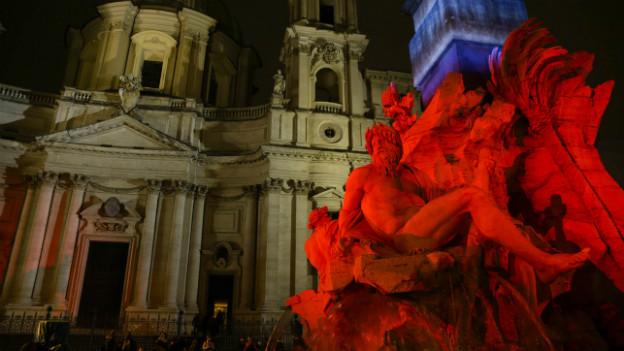 Eine Skulptur in Rom wird in verschiedenen Farben weihnachtlich beleuchtet.
