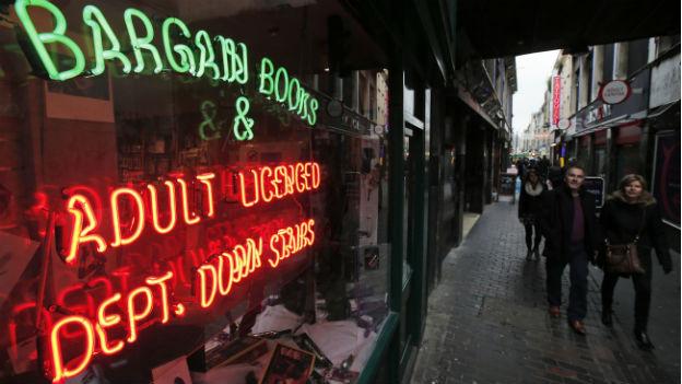 Das Bild zeigt ein Schaufenster mit Neon-Leuchtschrift in einer Gasse des Soho.