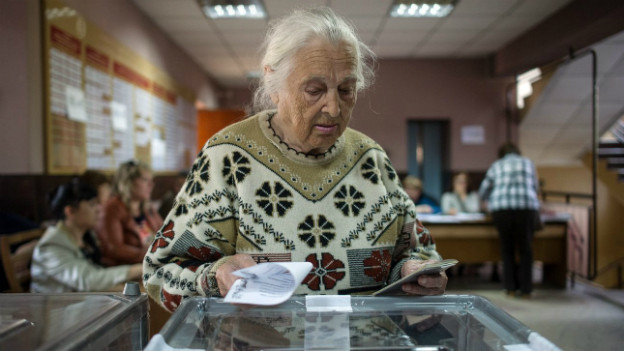 Eine alte Frau legt ihren Stimmzettel in die Wahlurne.