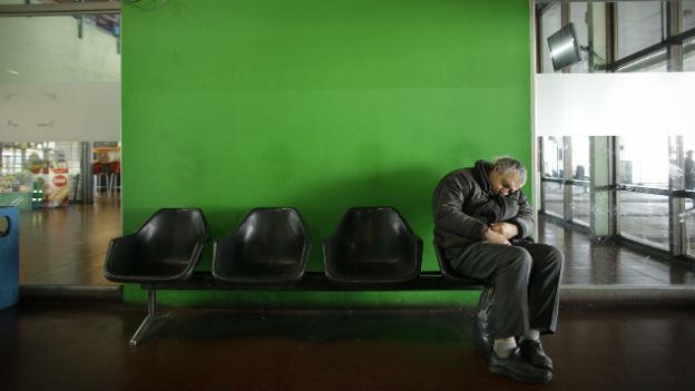 Ein Mann schläft auf einem Sitz vor einer grünen Wand in einem leeren Bahnhof