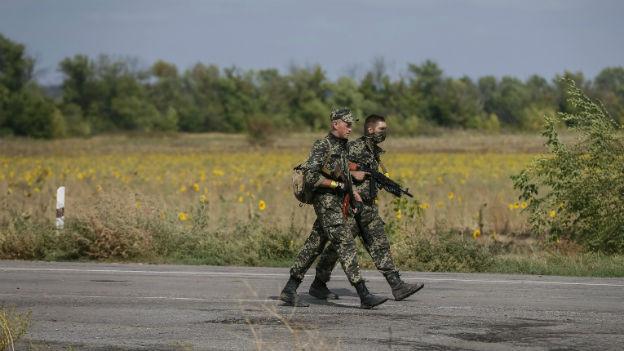 Zwei Soldaten der ukrainischen Nationalgarde patroullieren auf einer Strasse. Im Hintergrund sind eine Wiese und ein paar Bäume zu sehen.