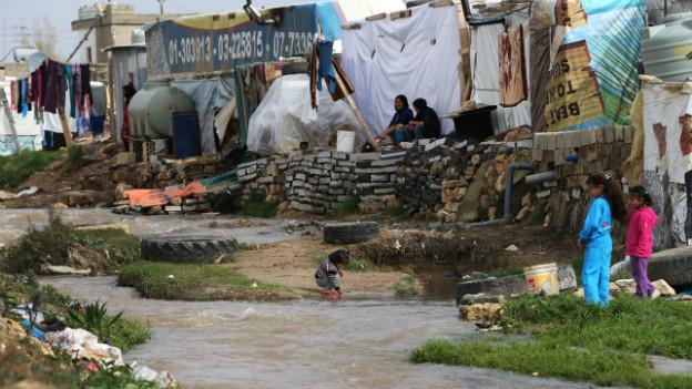 Ein Kind spielt an einem dreckigen Fluss in der Nähe eines Camps.