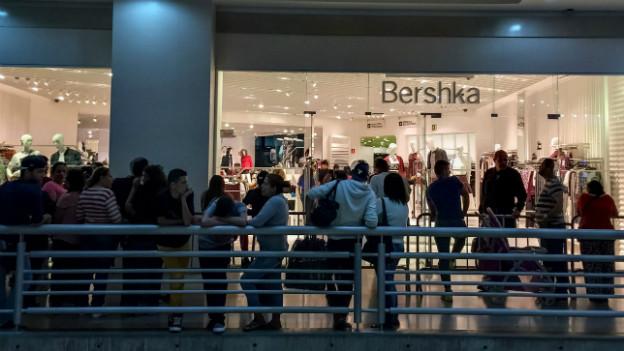 Eine Menschenschlange wartet vor einem Kleidergeschäft mit billigen Preisen in Caracas.