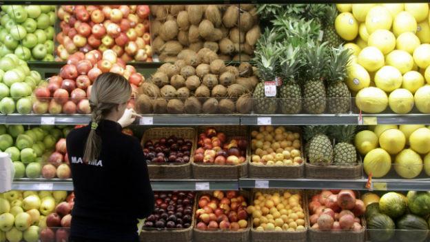 Eine Frau steht vor einer Auslage mit Früchten und wechselt die Preisschilder aus.