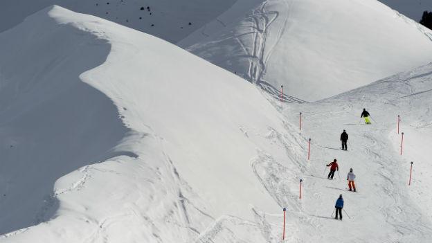 Skifahrer fahren weisse Hügel hinab.
