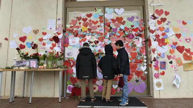 Drei Buben betrachten farbige Zettel mit Solidaritätsbekundungen beim Eingang zur Moschee in Uppsala.