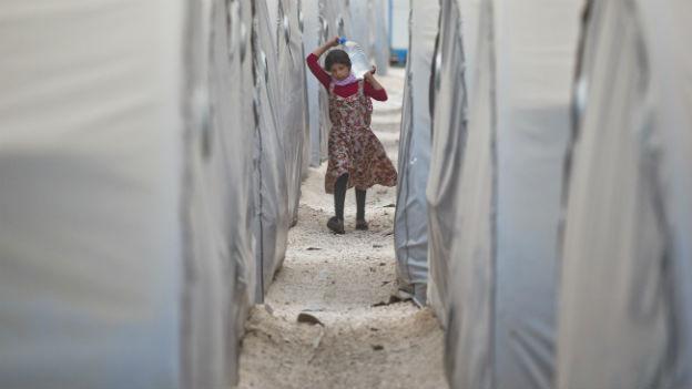 Mädchen läuft mit Wasserflasche zwischen Zelten.