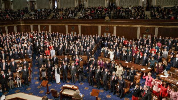 Parlamentarier/innen im Reprästentenhaus stehend mit erhobener Hand beim Eid ablegen.