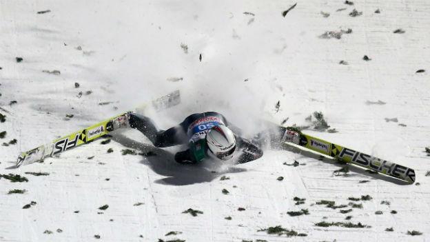 Skispringer SImon Ammann liegt nach Sturz im Schnee.