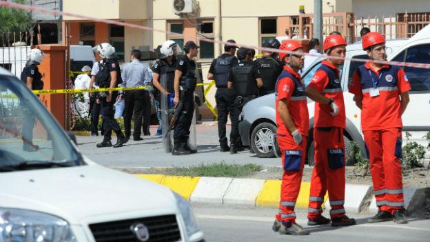 Sicherheitskräfte vor Absperrband und beschädigtem Gebäude.
