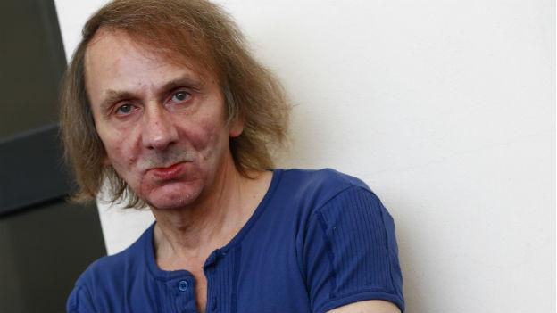 Das Bild zeigt ein Porträt des Schriftstellers Michel Houellebecq. Er hat halblange Haare und trägt ein blaues T-Shirt.