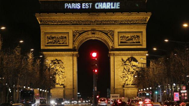 """Arc de Triomphe nachts mit Leuchtschrift """"Paris est Charlie"""""""
