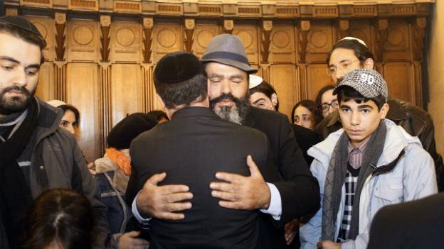 François Hollande umarmt einen trauernden Mann in einer Synagoge in Paris.