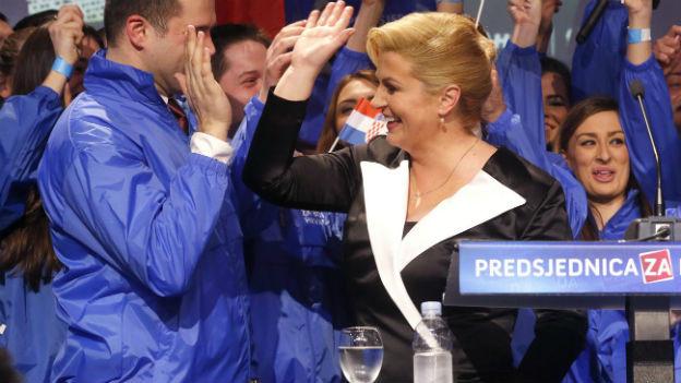 Kroatische Präsidentin in Siegespose vor jubelnden Anhängern.