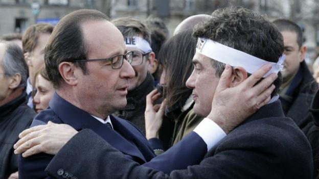 François Hollande umarmt Patrick Pelloux vom Satiremagazin Charlie Hebdo. Die beiden sind umringt von vielen anderen Menschen.