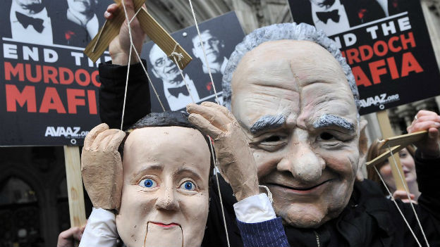 Ein Protestierender hält vor dem High Court in London Marionettenfiguren von Rupert Murdoch und David Cameron hoch.