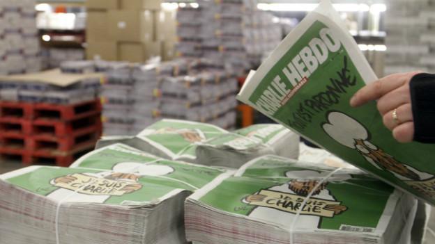 Ein Mann hält eine aktuelle «Charlie Hebdo»-Ausgabe in den Händen.