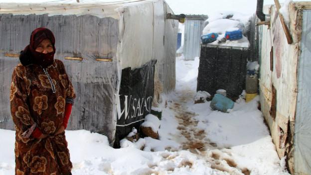 Eine Frau steht vor ihrem Zelt in einem Flüchtlingslager im Schnee.