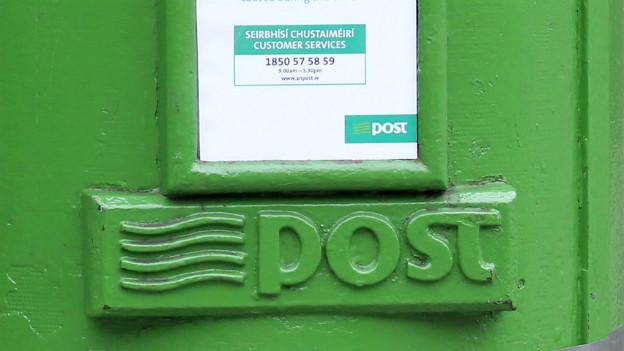 Eine Nahaufnahme eines irischen Briefkasten, zu lesen ist das Wort «Post».
