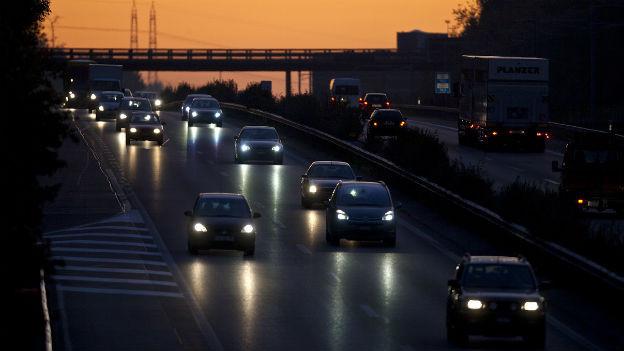 Autos mit Licht in der Dämmerung auf der Autobahn.