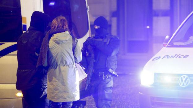 Polizisten im Scheinwerferlicht eines Polizeifahrzeugs.