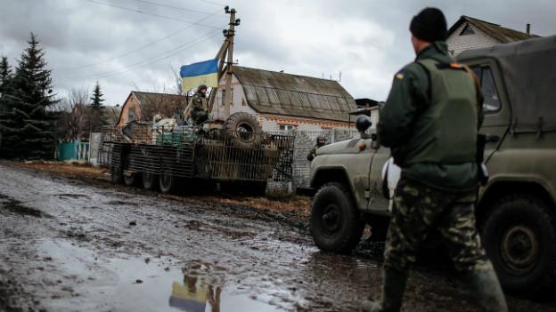 Ein ukrainischer Soldat bewacht seinen Jeep an einem Checkpoint.