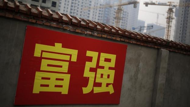Banner mit gelben chinesischen Schriftzeichen auf rotem Grund auf Mauer, im HIntergrund Hochhäuser im Bau.