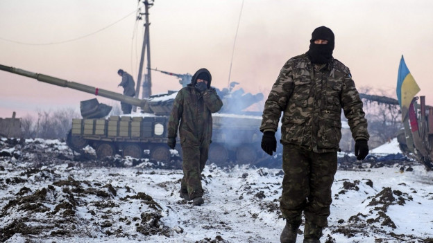 Zwei vermummte Soldaten auf verschneitem Feld, Panzer im Hintergrund.