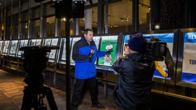 Aufnahme eines Fox-Journalisten, der im Newseum in Washington über die ausgestellten Charlie Hebdo-Karikaturen berichtet.