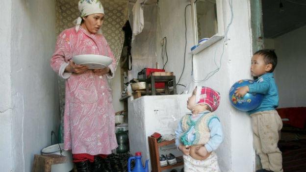 Mutter mit Schüssel in der Hand und zwei Kinder in der kleinen Küche