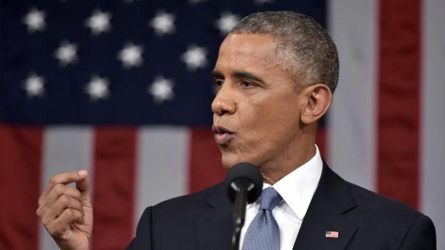 Man sieht Barak Obama hinter dem Rednerpult vor einer grossen US-Flagge mitten während seiner Rede