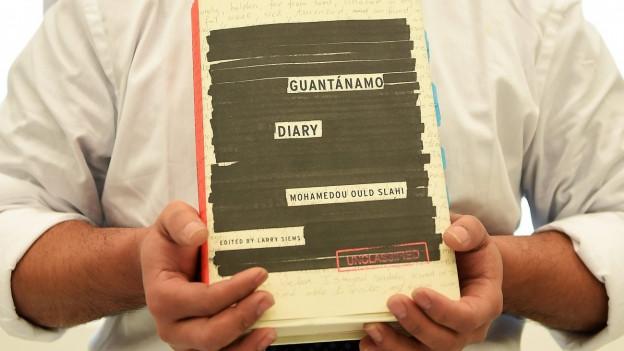 Das Bild zeigt eine Grossaufnahme des Buchs Guantanamo Diary, das jemand in den Händen hält.